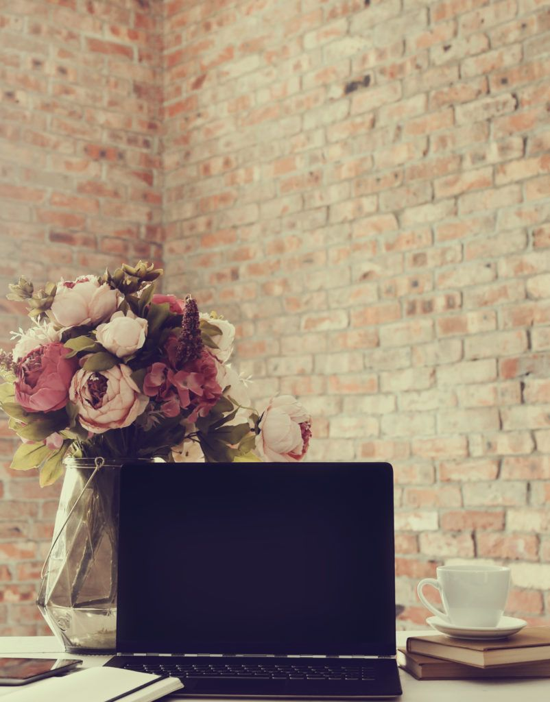 Computer with vase and brick wall